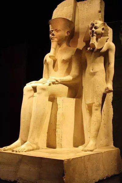 A limestone sculpture depicting the god Amun (larger) and Tutankhamun
